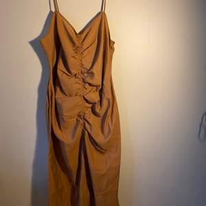 En V-Ringad klänning men regler bara smala axelband och rynkad söm på fram och baksidan och en dold dragkedja på sidan. Klänningen är aldrig använd, den är i storlek 50 men liten i storleken.