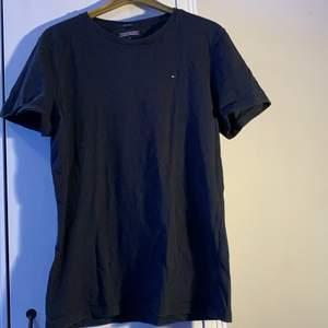 Svart T-Shirt från tommy hilfiger, litet hål på höger sida av magen men annars bra skick. Storlek 176