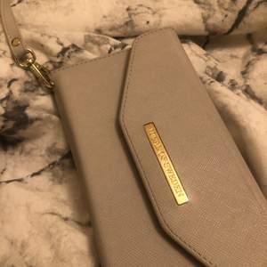 ett grått plånboksfodral från ideal of sweden. har fläckar på!