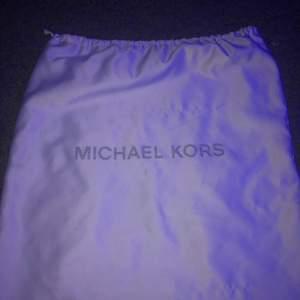 En vit Michael kors väska gjort av silke. Funkar jätte bra att ha kläder i eller annat.