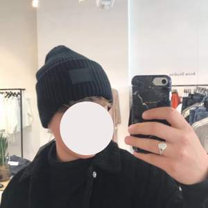 """Acne Studios - Face logo beanie black Använd denna vintern med ren och som ny! """"Acne Studios black oversized beanie is knitted in a thick rib-stitch from soft wool and features a tonal face-embroidered patch."""" Nypris är 1100kr"""