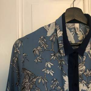 Superfin blå och mönstrad skjorta. Storleken är okänd men jag skulle säga Medium. Väldigt snygg att knyta i midjan. Köparen står för frakten!