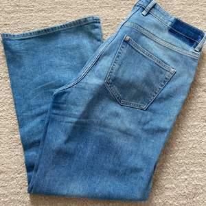 Sparsamt använda ankellånga stretchiga jeans. De har högmidja och är vida i modellen. Är i storlek 40.