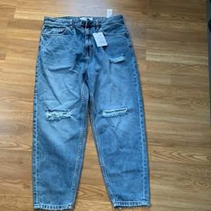 Säljer ett par nya blåa mom jeans från bershka. Dessa byxor är i storleken 42 och är helt nya! Säljs pågrund av fel storlek!
