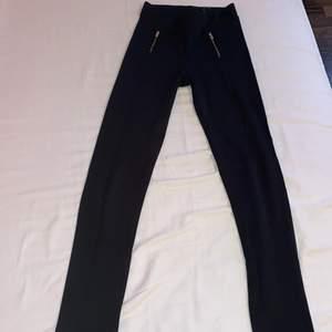 Svarta leggings med fin guldig detalj. Lite tjockare material med högre kvalitet än vanliga leggings. Har en svart söm längs vardera ben. Litet hål på höger ben.