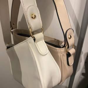 """Två super fina väskor som ena är vit och andra beige/ljus rosa? Säljer pga för många väskor! 90kr + frakt för båda väskorna, man kan absolut köpa bara en💖 perfekt längd under """"armen"""""""