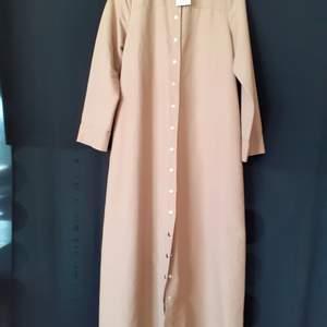 Oanvänd kappa som kan användes som ytterkläde i höst och vår, linknande som en trenchcoat. Storleken är 38 men stor i storleken. (Det var förstor för mig) Köparen betalar frakten.