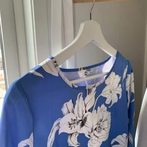 En blå sommarklänning med vita blommor. Aldrig använd utan har endast provat den. Den har inte kommit till användning och därför säljer jag den. Men som sagt passar super bra nu vid sommaren/våren. Vid frågor hör gärna av dig.💙