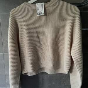 Jättefin beige stickad tröja. Extremt fint skick, helt oanvänd, till och med prislappen kvar! Lite kroppad tröja i en sjukt fin beige färg! (Köparen står alltid för frakten)