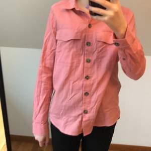 Rosa skjorta från H&M divided storlek 32. (Ej struken på bilderna) köptes 2019 tror jag men använd max 10 gånger, fint skick. 8 knappar och 2 bröstfickor. Används inte längre tyvärr. Möts upp i Borås eller fraktar, köparen står för frakten. Skriv privat för fler bilder!