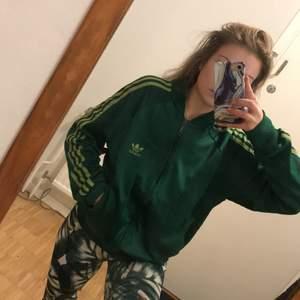 Grön adidas tröjja med ljusgröna stripes.. Den är använd men inga hål eller skador finns. Otroligt bekväm, oversize för mig som är en xs/s. Säljes motvilligt pga flyttstädning..