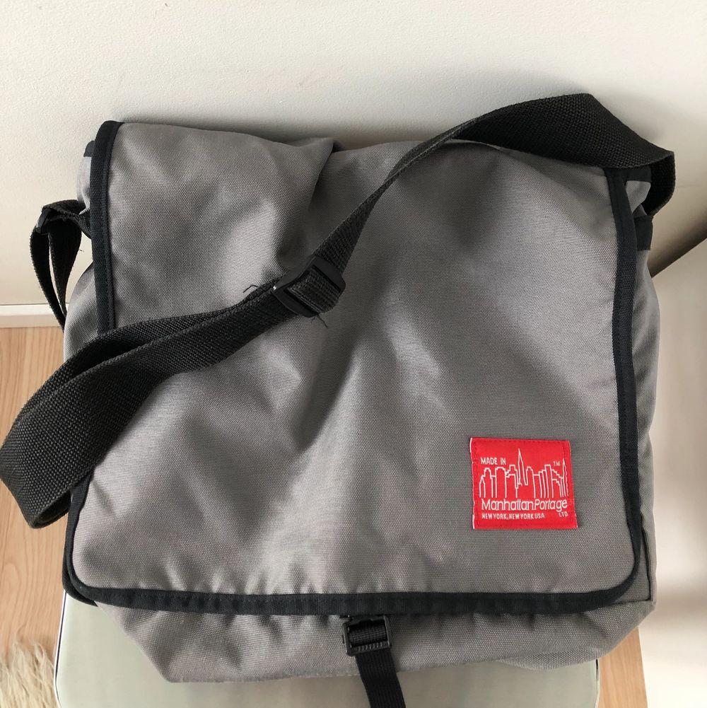 Säljer en Manhattan Portage messangerbag. Köpt secondhand så den är i användt men bra skick!👍🏻 Den är rymlig och har flera stora fack, och kan därför rymma dator etc. (Färg: Grå) Lite frakt tillkommer✨. Accessoarer.