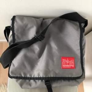 Säljer en Manhattan Portage messangerbag. Köpt secondhand så den är i användt men bra skick!👍🏻 Den är rymlig och har flera stora fack, och kan därför rymma dator etc. (Färg: Grå) Lite frakt tillkommer✨
