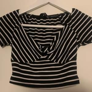 Randig t-shirt topp i bra skick. Den har justerbara knytband som går över bröstet precis som visas på bilderna. Den är knappt använd. Säljer toppen pga att den inte kommit till användning och är inte min typ av topp som passar bra på mig.