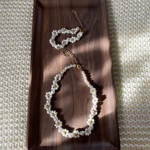 Matchande halsband & armband i vitt och guld. Elastisk tråd kombinerad med guldkedja. Storleksmässigt - choker men lite justerbart. Armband är också justerbart. Egentillverkat och aldrig använt.