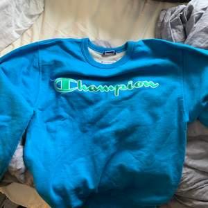 Blå snygg champion sweatshirt med grön text💖Köpt i Miami förra året och säljer nu då ja inte använder den. Super bra skick!! Köpt på mansavdelningen så även om det är en liten storlek så blir det en L på mig som tjej. Kan mötas upp eller posta💖 Nypris 450kr