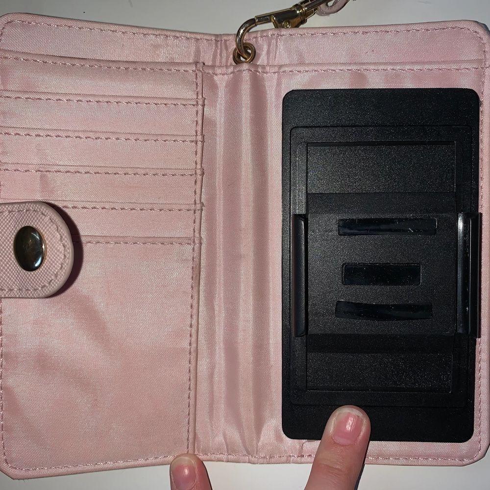 Ett rosa plånboksskal med korthållare i och sedelhållare. Man sätter på mobilen genom att dra i kanterna på svarta delen och sätter på mobilen. När man ska ta bild men bakkamera så trycker man bara upp den svarta delen medans mobilen fortfarande sitter på. Skalet har också ett band som man kan stoppa igenom handen. Skalet är runt 2 år gammalt. . Övrigt.