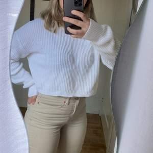 En vit stickad tröja i storlek M.