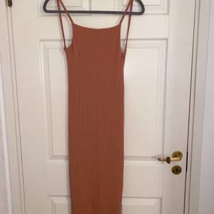 Oanvänd laxfärgad tajt klänning, klänningen är lång till knäna, öppen vid ryggen.