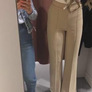 Ett par skitsnygga beiga kostymbyxor från Gina tricot. Köpta innan skolavslutningen förra året. Säljer då dom tyvärr har blivit för korta för mig. Storlek S. Resår i midjan och väldigt skönt material. Utsvängda i benen. Köparen står för frakten🤍
