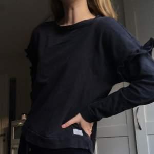 Svart, simpel tröja med volang från I dig denim! Sparsamt använd