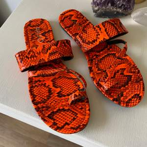 Skitcoola neon orangea ormmönstrade sandaler från EGO. Använda ett par gånger men i fint skick!