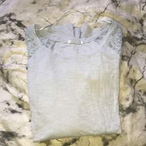 En blå tröja med detaljer på axlarna