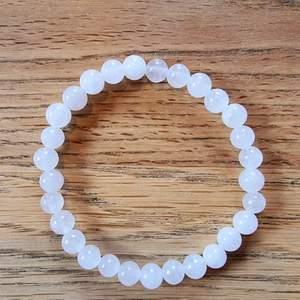 Armband med 6 mm stora kristallpärlor av vit jade.  Rundslipade stenar trädda på elastisk tråd. Ca 16 cm omkrets. Skickas i vadderat kuvert via postnord.