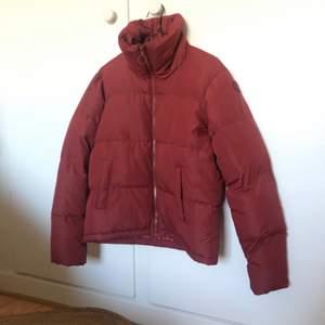 En roströd puffer jacket som passar strl 34-36. Köpt på Stadium. Sparsamt använd så fint skick. Har lite vita fläckar på kragen från smink, men det går nog att få bort. Kan skicka bilder om så önskas.