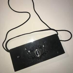 Svart avlång handväska i nyskick dvs aldrig använd. Det sitter fast ett långt band oxå för att ha över axeln men man kan inte ta av det långa. Det korta kan man däremot klicka loss om så önskas