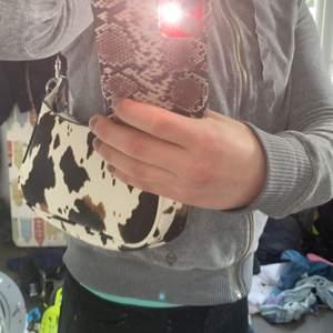 Väska med ko mönster kedja fås med och axelbandet går att plockas av och på svart inuti väskan använd Max 2 gånger. säljer pga använder aldrig o behöver pengarna köpare står för frakten men om man köper för 150 ingår frakt 💕💕buda gärna i kommentarerna