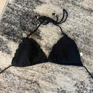 En svart bikini från Nelly med volanger vid sidorna🌺 bra bikini att ha i garderoben, jag har dock för många därför säljer jag denna som knappt används! Använd max tre gånger. Går att köpa delarna separat för 50kr ☀️🥰