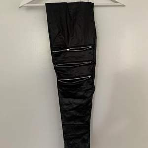 Svart tights i imitationsskinn med dragkedjor på knäna som detaljer. Snygga till fest!