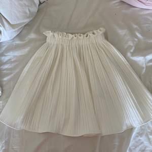 En jättefin, vit volangkjol från ginatricot! Väldigt stretchig resår, så passar flera storlekar! Säljer pga inte riktigt min stil. Bra skick!  Nypris 400-500 kr. Frakt tillkommer!