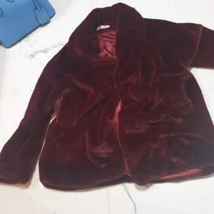 Mysig vinter jacka i vinröd färg jag tror ena knappen gått sönder men jag brukar alltid ha den med ett bälte ändå! Superfin. Ganska lång när man låter den hänga men man kan puffa upp den om man har ett bälte