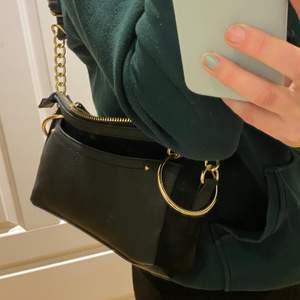 En svart väska med Guld detaljer använd en gång så fint skick. Går att ha som borde baguette och lite längre💛