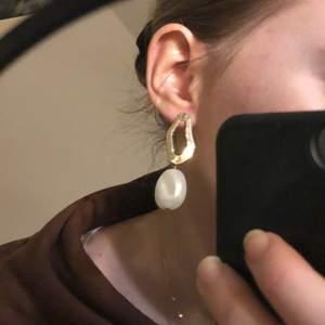 supervackra örhängen med en abstrakt guldoval och en stor bucklig pärla, jättefina till fest eller till en vit t-shirt och jeans!