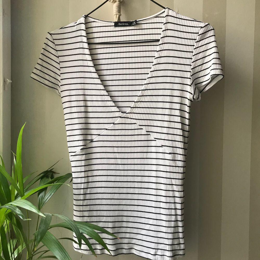 Riktigt snygg minimalistiskt-shirt från Bershka. Superfina detaljer vid brösten. Endast använd ett fåtal gånger och är därför i toppskick! T-shirten är i storlek M men passar XS-M 💛. T-shirts.
