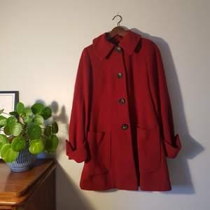 Röd vinterkappa med stora knappar. Lite i stil med rödluvan. Väldigt varm och skön.