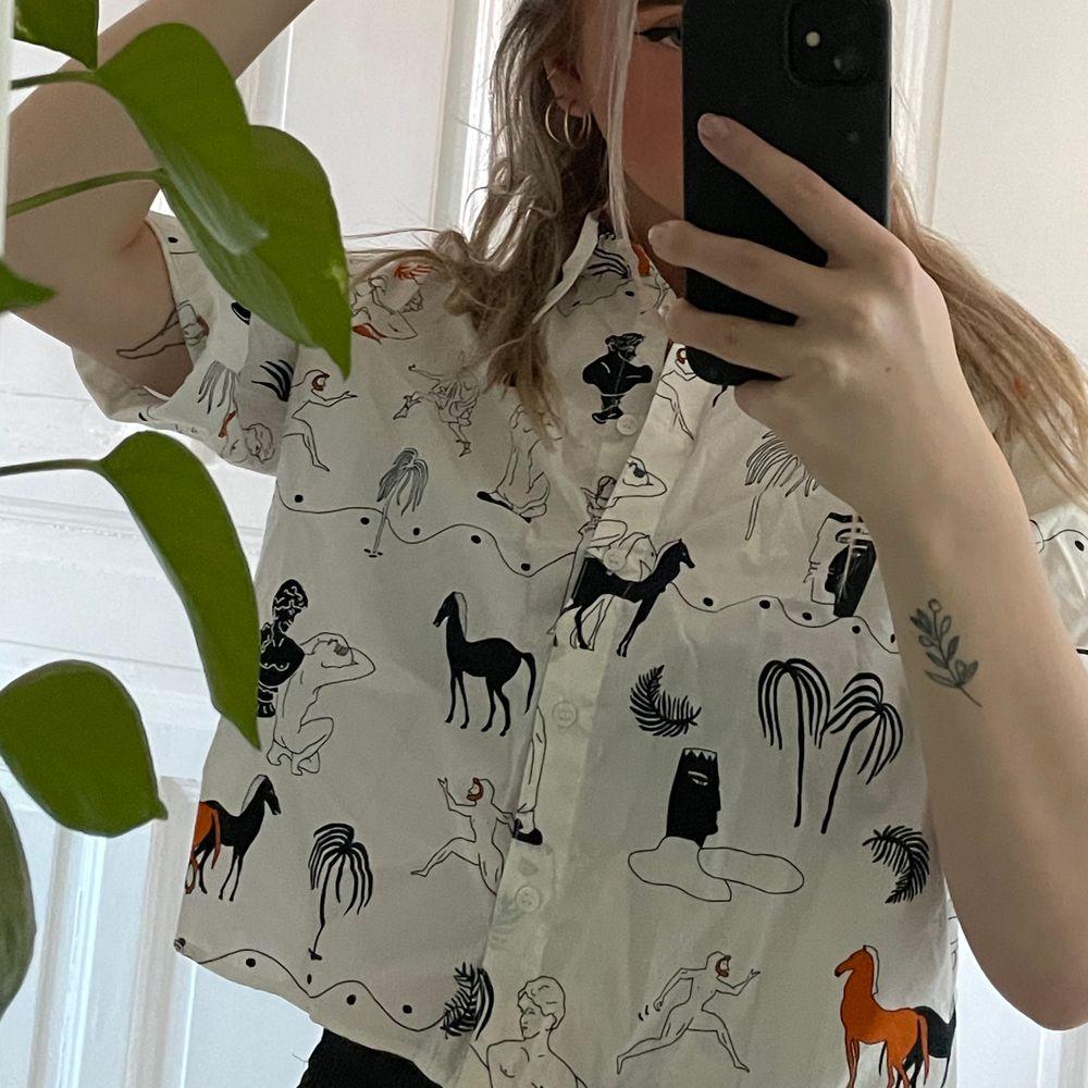 En boxformad, kort t-shirtskjorta från Monki med ett mönster med lite allt möjligt på! Aldrig använd så superfint skick, den är dock köpt begagnad. Köparen står för frakten som tillkommer! 💖. Skjortor.