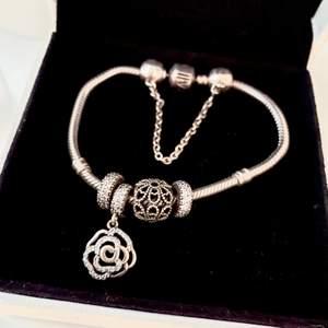 Pandora armband som är använd väldigt lite. Säljer tillsamans med charms på bilden.  Storlek 15 på armbandet