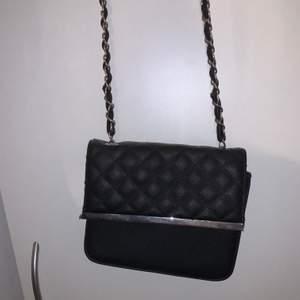 Svart väska med silver detalj och långt band. På andra bilden kan man se hur stor/lång den är.