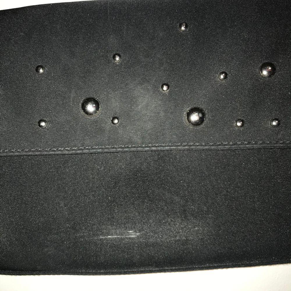 Svart handväska köpt second, den har silverdetaljer på framsidan och stängs med magnet. Den har ett par vita streck på framsidan men det märks knappt. Möta upp i Stockholm eller står köparen för frakten💞 . Väskor.