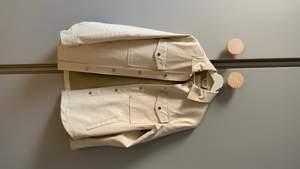 Beige skjorta i snygg skinnimation. Snygg passform, ser lyxig ut. Stl XS men upplevs som oversize så passar fint en S.