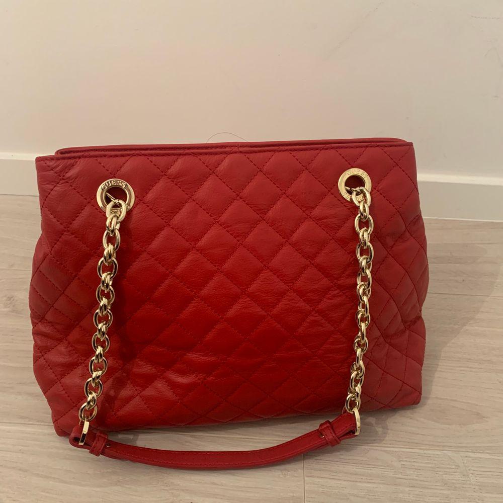Röd Guess väska med guldiga detaljer. köptes för 1200 i Guess butik i Norge. Använd en gång . Väskor.