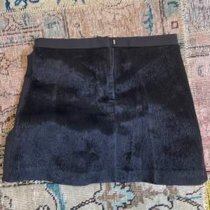 Svart kjol med pälsimitation på framsidan och svart tyg på bak. Kjolen är den House of Dagmar i storlek 36.