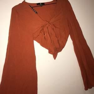 Knytblus i en orange/roströd jättefin färg. Vida ärmar