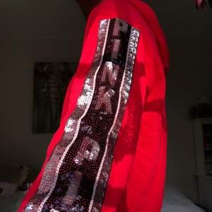 Röd  hyfsat tunn hoodie från pink med coola paljett-detaljer. Jättebra skick! Står ej strl men skulle säga S/M. Frakt tillkommer