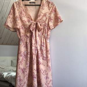 Rosa blommönstrad klänning från Gina Tricot med knytning framtill i polyester. Väldigt lätt och luftig🌸