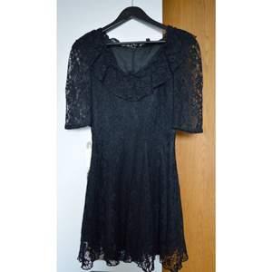 Söt spetsklänning med markerad midja. 100% polyester.